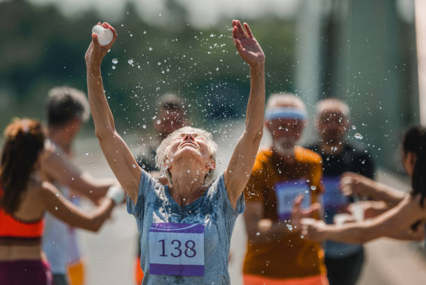 Senior marathon runner refreshing herself with water during a race. Senior woman running a marathon on the road and refreshing herself with water from a cup. There are people in the background. groyne stock pictures, royalty-free photos & images