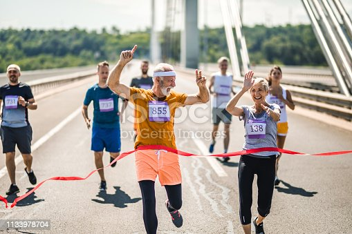 Successful mature marathon runners crossing the finish line with their arms raised.