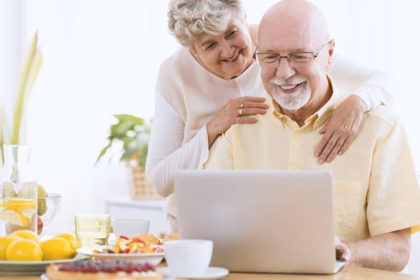 senior ehe suchen auf laptop - senior bilder wasser stock-fotos und bilder