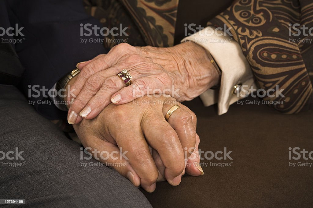 senior married couple holding hands closeup: sixty years of fidelity royalty-free stock photo