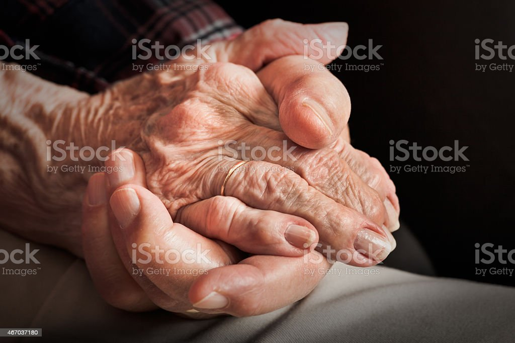 senior married couple holding hands closeup: sixty years of fidelity stock photo