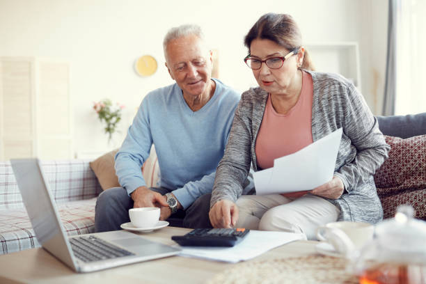 Senior married couple in casual clothing sitting on sofa in living room and viewing papers while calculating monthly expenses together stock photo