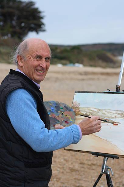 senior reifer künstler malen by the sea - senior bilder wasser stock-fotos und bilder