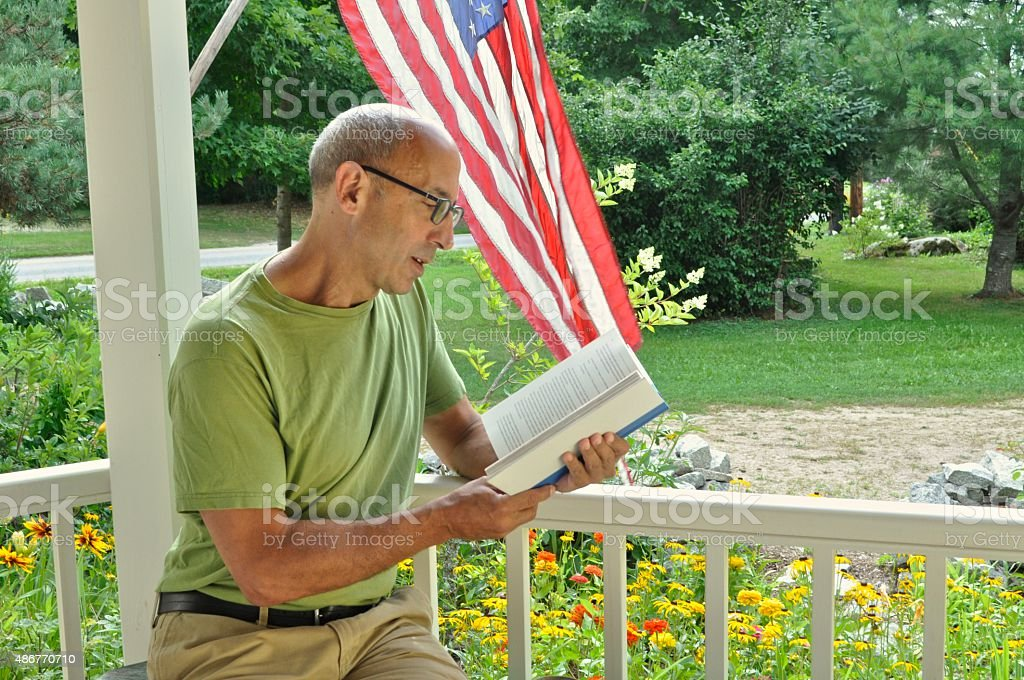 Senior Mature Man Reading Book on Porch with American Flag stock photo