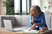 istock Senior mature older woman watching business training, online webinar on laptop computer remote working or social distance learning from home. 60s businesswoman video conference calling in virtual chat 1281725866