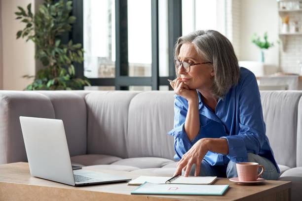 starsza starsza kobieta oglądająca szkolenia biznesowe, internetowe seminarium internetowe na komputerze przenośnym do zdalnej pracy lub nauka na odległość społeczną z domu. 60s bizneswoman wideo konferencja rozmowy w wirtualnym czacie - dojrzały zdjęcia i obrazy z banku zdjęć