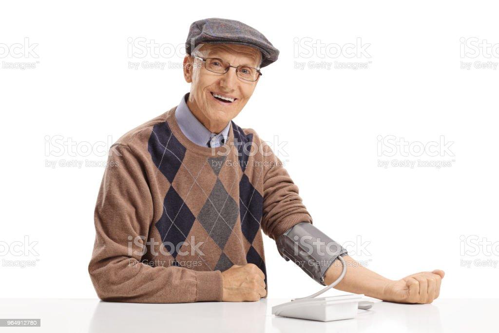 資深測量他的血壓和看觀景窗 - 免版稅70多歲圖庫照片