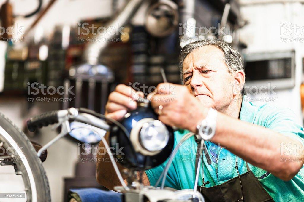 Senior mechanic fixing a motorcycle stock photo