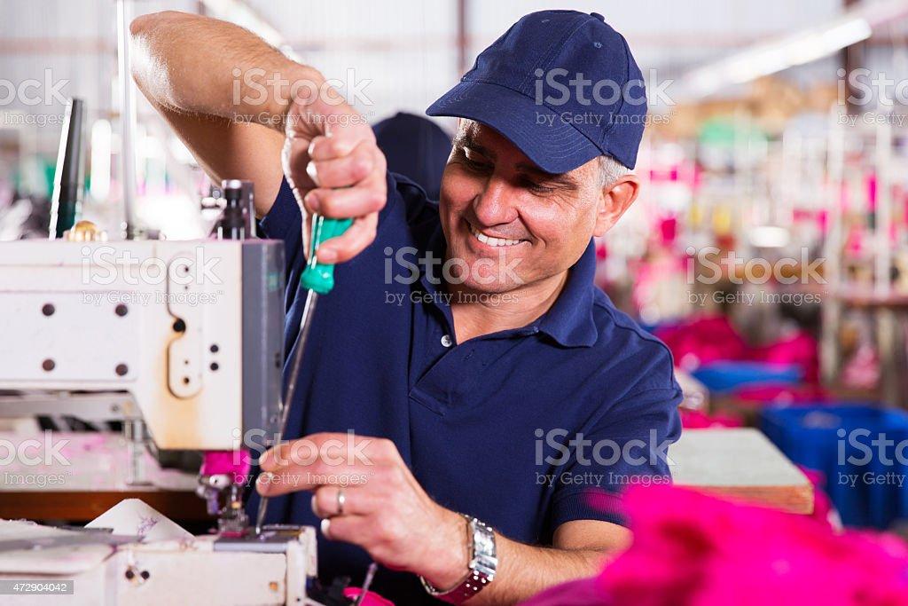 senior mechanic repairing industrial sewing machine stock photo