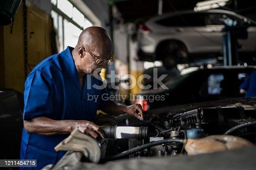 Senior mechanic woman checking car in car repair shop