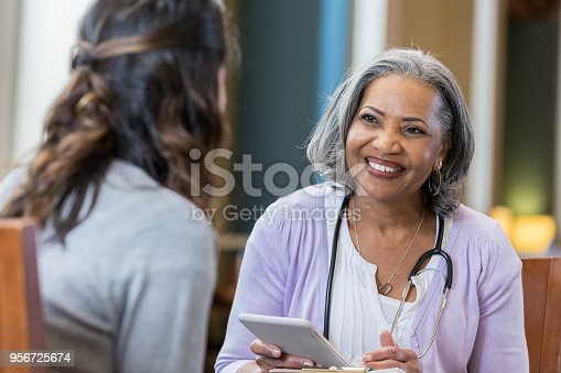 A cheerful senior woman wears a stethoscope as she sits with an unrecognizable woman during an interview.  She holds a digital tablet.