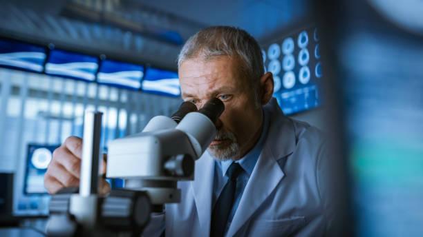 senior medical research scientist suchen unter dem mikroskop im labor. neurologe rätsel des verstandes und des gehirns. im labor mit mehreren bildschirmen zeigen, mri / ct gehirn bilder scannen. - krebs tumor stock-fotos und bilder