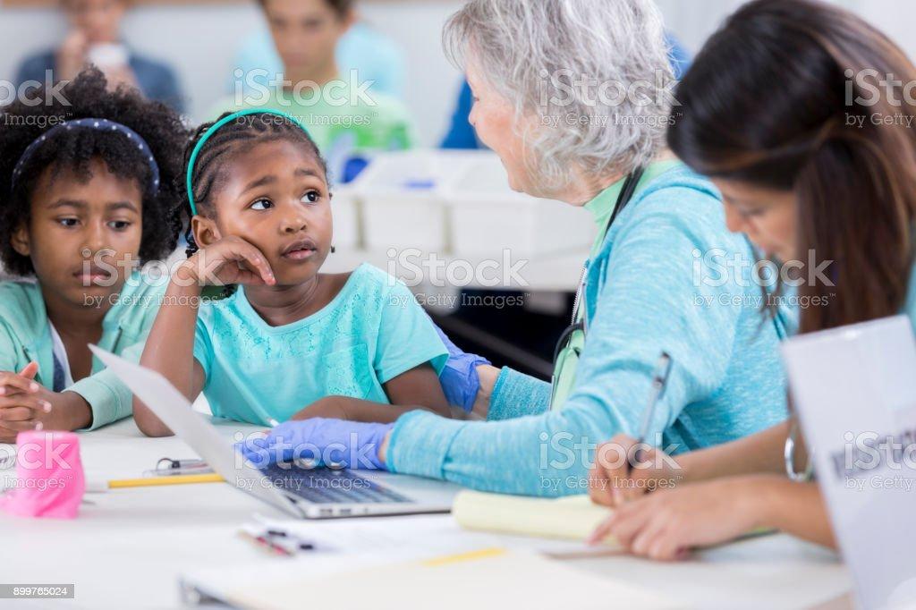 Senior medical volunteer interviews young girl stock photo