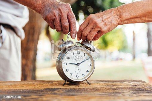 Senior men and senior woman with clock