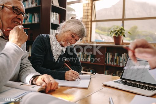 Senior woman writing notes sitting in a library with her male colleagues. Elderly people discussing and learning in a university college.