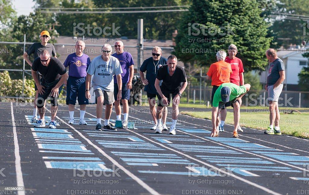 Senior men await a signal to start 100-meter race stock photo