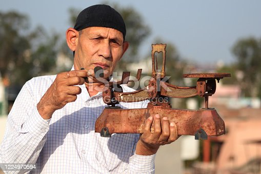 Old man of Indian Ethnicity carrying weight scale in hand outdoors. A balance is a device to measure weight or mass. These are also known as mass scales, weight scales, mass balances, weight balances, or simply scales, balances, or balance scales.