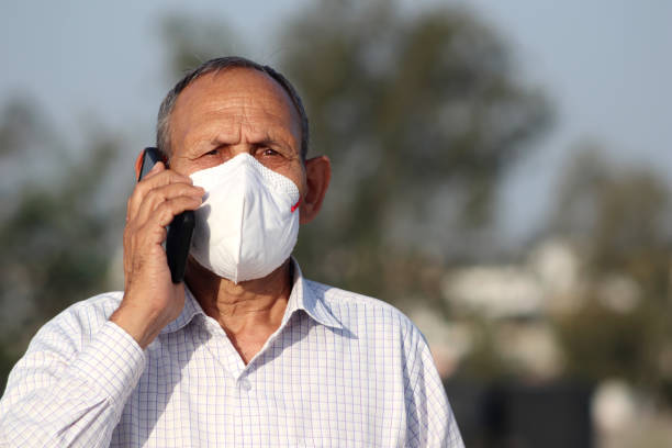Senior men covering his face with pollution mask for protection against COVID-19 and talking on mobile phone stock photo