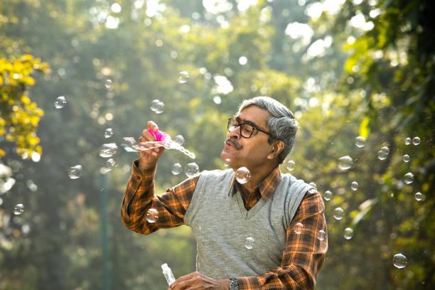Senior men enjoying blowing bubbles at park stock photo