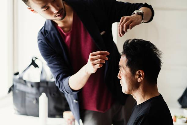 年配の男性が美容室でスタイリング髪を持っています。 - 美容室 ストックフォトと画像