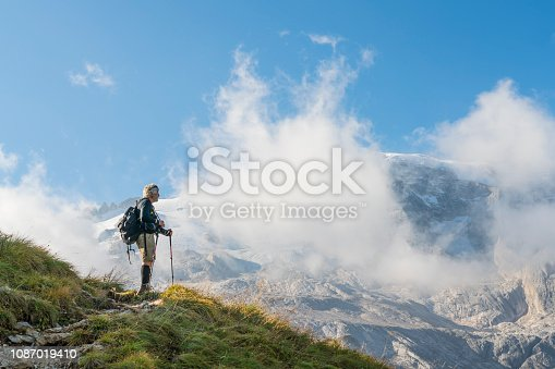 Senior man hiking along hills opposite to the Marmolada in autumn. Sunny clear blue sky. Dolomites, Northern Italy.