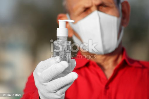 Senior men of Indian ethnicity holding hand sanitizer in hand and wearing pollution mask against Coronavirus. Promoting people use hand Sanitizer to protect themselves from virus infection in Corona Virus crisis.