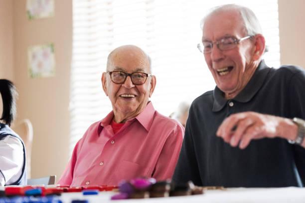 Senior men laughing playing bingo together stock photo