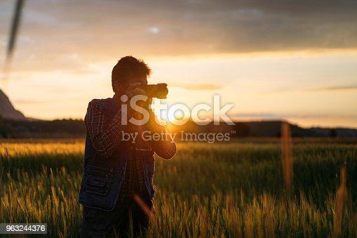Senior men photographing sunset