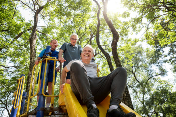 Senior men playing at a playground slide Senior men playing at a playground slide young at heart stock pictures, royalty-free photos & images