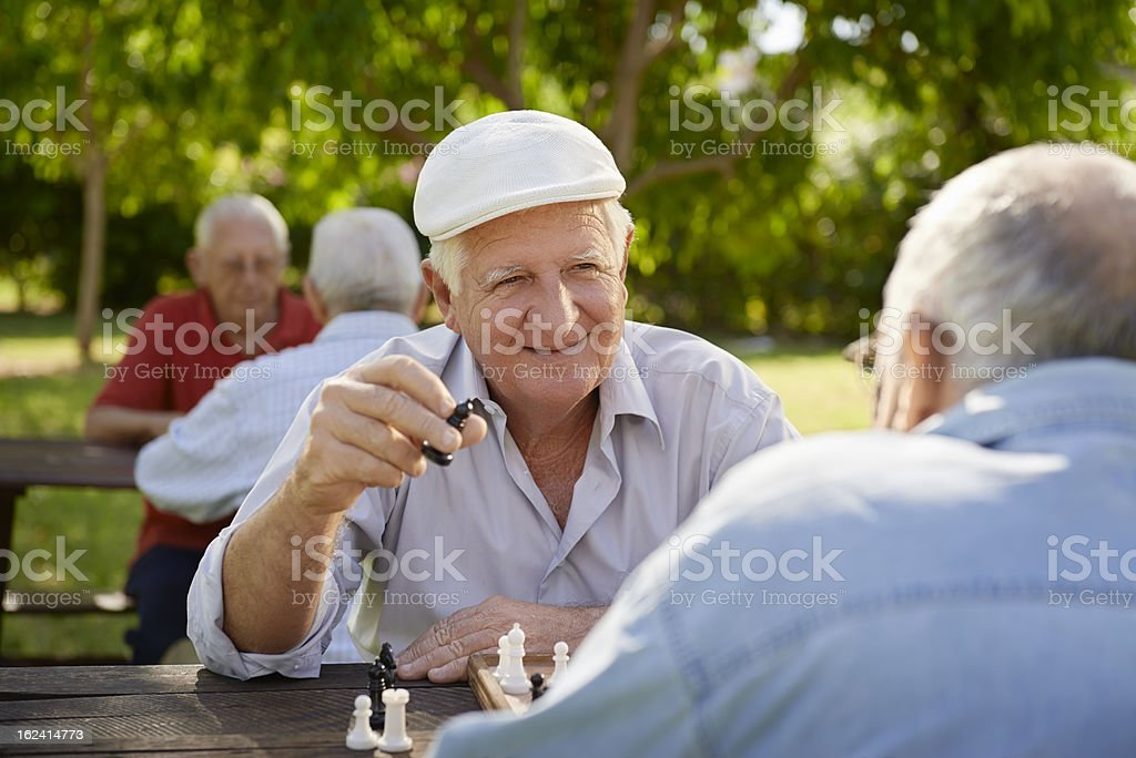 Senior men playing chess in a park with blurred men in back stock photo