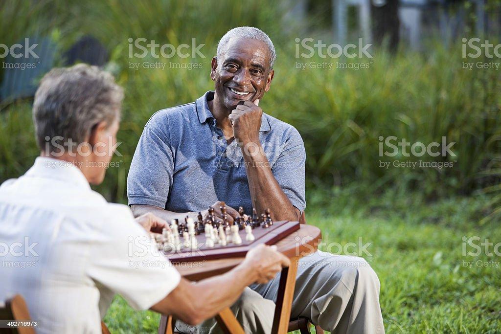 Senior men playing chess in park stock photo