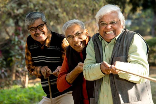 Senior men playing tug of war stock photo