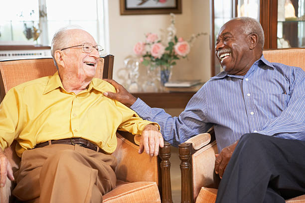 Senior men relaxing in armchairs Senior men relaxing in armchairs and laughing together retirement community stock pictures, royalty-free photos & images