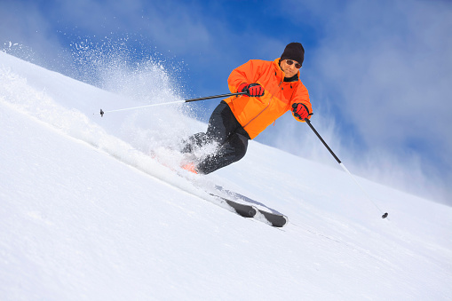 Senior men snow skier skiing on sunny ski resorts