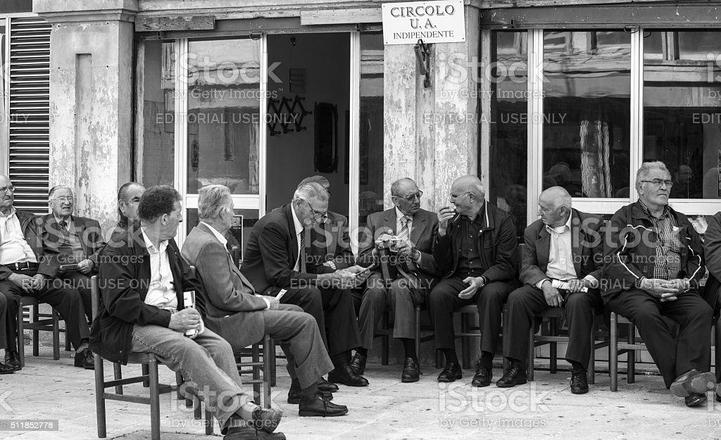 Senior Men Socialize on Piazza in Sicily stock photo