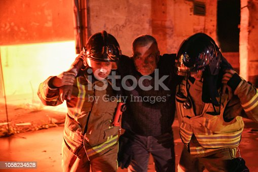 Two firefighters rescuing a victim of a fire with arms around them and helping him to walk away from the fire. Senior man with fear on his face.