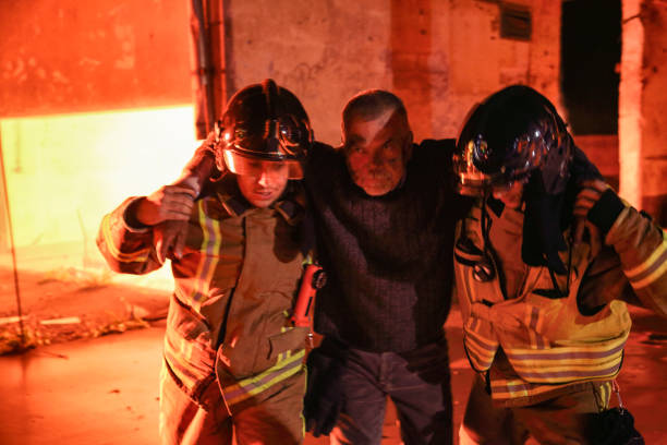 senior men victim of a fire being rescued by two firefighters - victim stock pictures, royalty-free photos & images