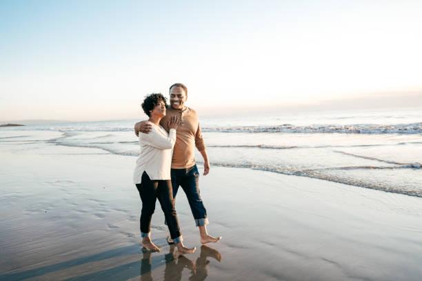 ledande män som gick med ledande kvinnor på stranden - middle aged man dating bildbanksfoton och bilder