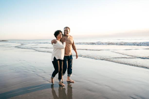 ledande män som gick med ledande kvinnor på stranden - senior walking bildbanksfoton och bilder