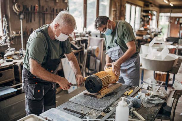 Senior men with protective face masks rebuilding an engine in workshop stock photo