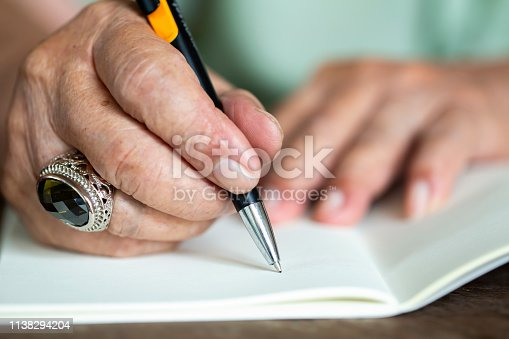 Senior men's hand writing letter on ivory colour paper, Notebook,  A black mix silver pen, On wooden background, Close up & Macro shot, Selective focus, Stationery concept