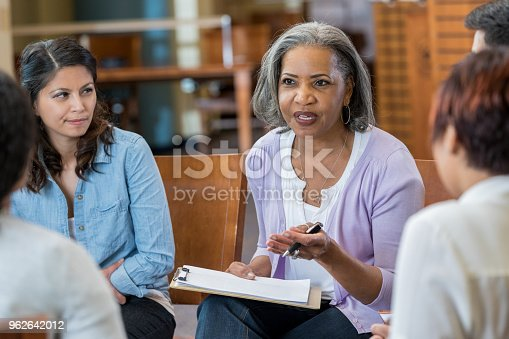 istock Senior mental health professional facilitates support group 962642012