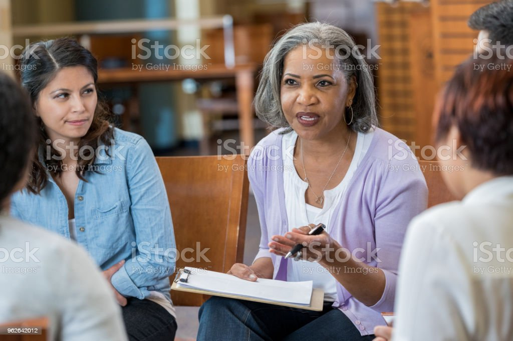 Senior mental health professional facilitates support group stock photo