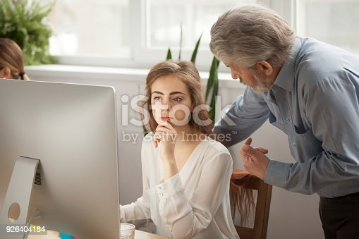 926404274 istock photo Senior mentor teaching young female intern using computer in office 926404184