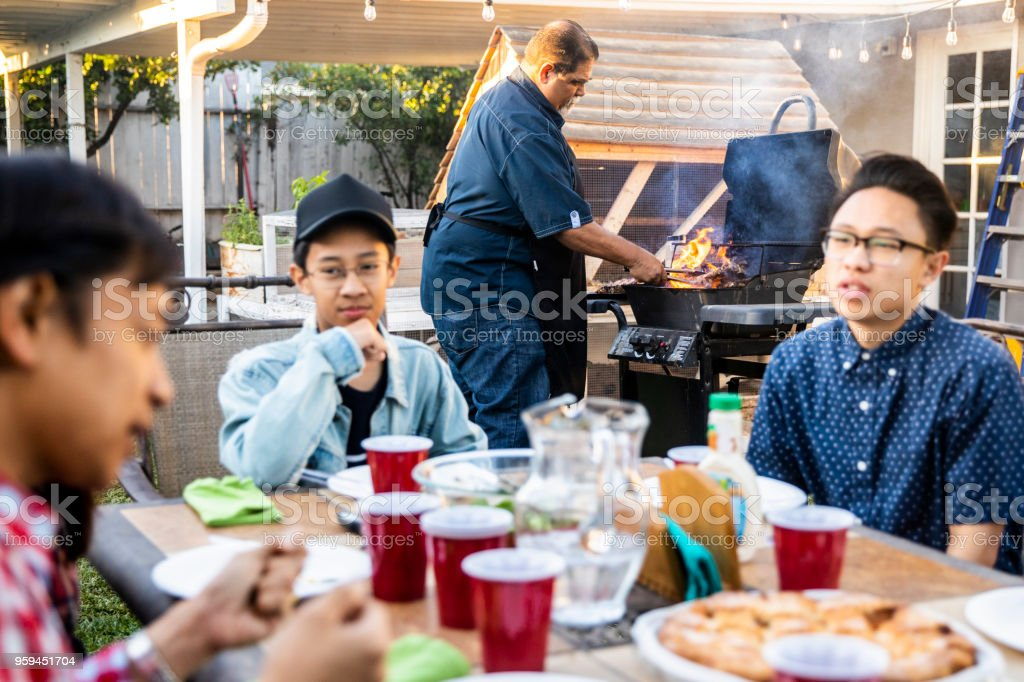 Senior Mexican Man Grilling Steaks stock photo
