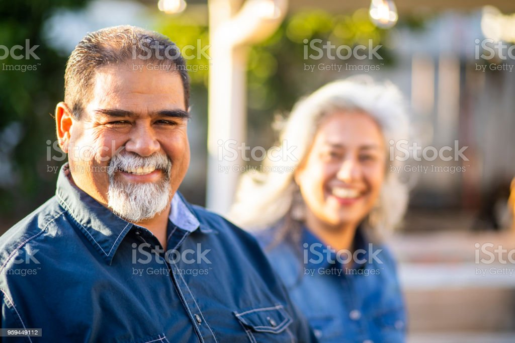 Senior Mexican Man Smiling with Wife in the Background stock photo