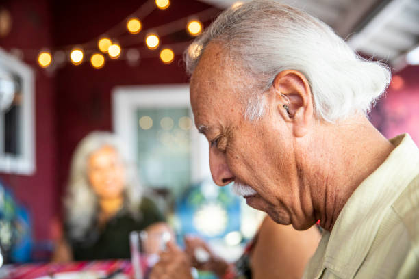 senior mexican man with hearing aid at dinner - hearing loss stock pictures, royalty-free photos & images