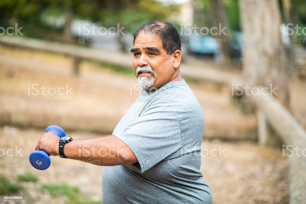 Senior Mexican Man Working Out Lifting Weights stock photo