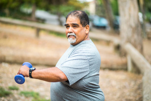 Senior Mexican Man Working Out Lifting Weights A senior mexican man working out lifting weights only senior men stock pictures, royalty-free photos & images