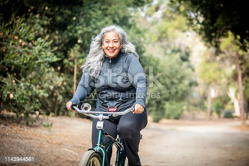 851958232 istock photo Senior Mexican Woman Riding Bicycle 1143944561